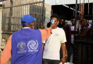 IOM staffer checks the temperature of Ethiopian migrants as they leave an IOM shelter before they were flown back to Ethiopia, in Aden