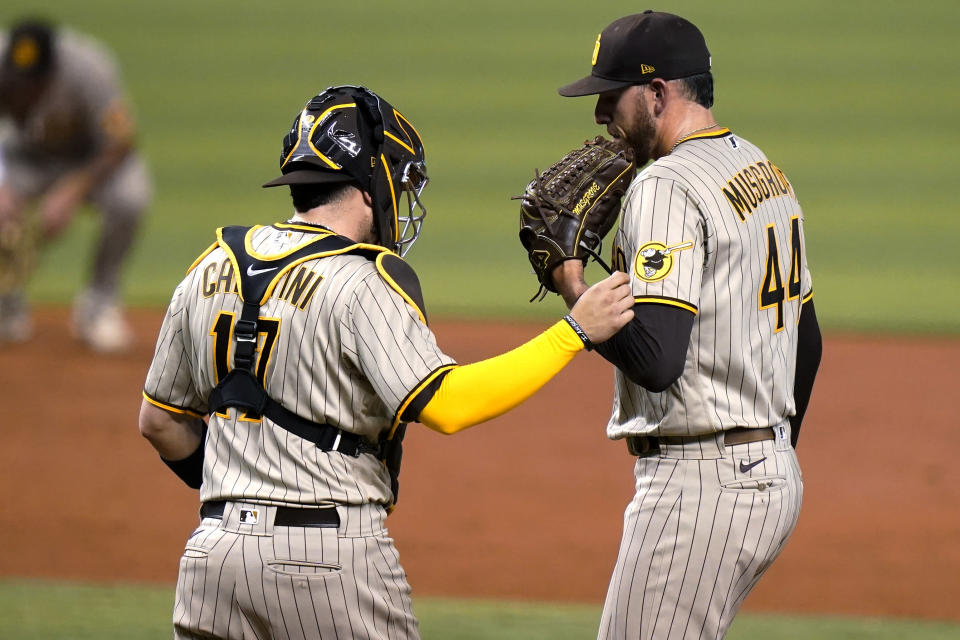 San Diego Padres catcher Victor Caratini (17) talks with starting pitcher Joe Musgrove (44) during the third inning of the team's baseball game against the Miami Marlins, Friday, July 23, 2021, in Miami. (AP Photo/Lynne Sladky)