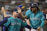 Seattle Mariners' J.P. Crawford, right, is congratulated by manager Scott Servais, left, and teammates after scoring a run against the Oakland Athletics during the third inning of a baseball game in Oakland, Calif., Monday, Sept. 20, 2021. (AP Photo/Jeff Chiu)