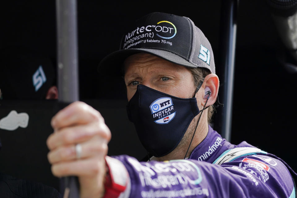 FILE - Romain Grosjean, of Switzerland, talks with a crew member before a warm-up session for the IndyCar auto race at Indianapolis Motor Speedway in Indianapolis, in this Saturday, May 15, 2021, file photo. Former Formula One driver Romain Grosjean, who moved to IndyCar this year, decided to give it a try after watching the Indianapolis 500 on television and tested at Gateway last month in advance of his debut. (AP Photo/Darron Cummings, File)