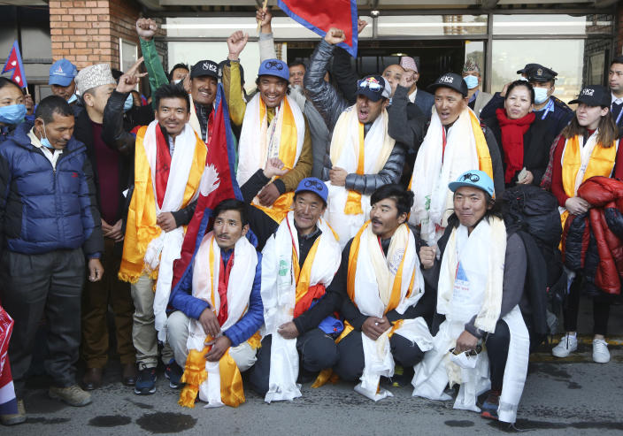 The all-Nepalese mountaineering team that became the first to scale Mount K2 in winter pose for the media as they arrive at Tribhuwan International airport in Kathmandu, Nepal, Tuesday, Jan. 26, 2021. (AP Photo/Niranjan Shrestha)