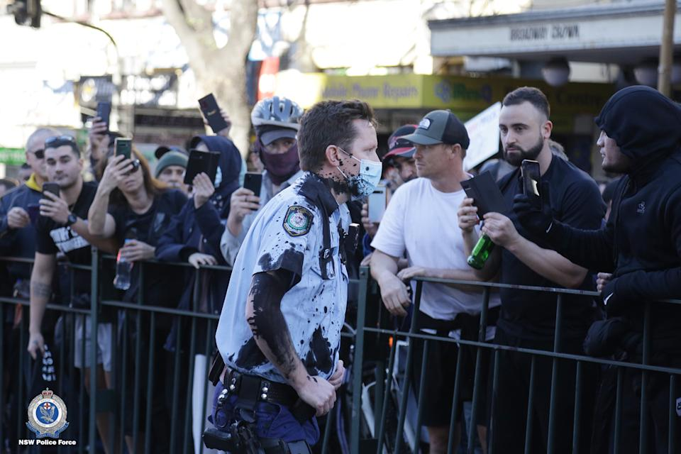 An officer seen with black substance thrown on him during the protest. Source: NSW Police