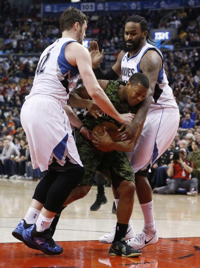 Toronto Raptors' Kyle Lowry moves between Minnesota Timberwolves' Kevin Love, left, and Ronny Turiaf during the first half of an NBA basketball game Friday, Jan. 17, 2014, in Toronto. (AP Photo/The Canadian Press, Mark Blinch)