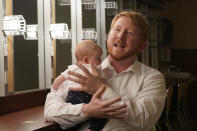 Democratic gubernatorial candidate, Del. Lee Carter, D-Manassas, gestures as he holds his baby girl, Charlotte, during an interview prior to the last primary debate in Newport News, Va., Tuesday, June 1, 2021. Carter faces four other Democrats in the primary June 8. (AP Photo/Steve Helber)