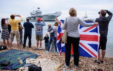 Members of the public gather to witness the arrival of the HMS Queen Elizabeth  - Credit: Leon Neal/Getty