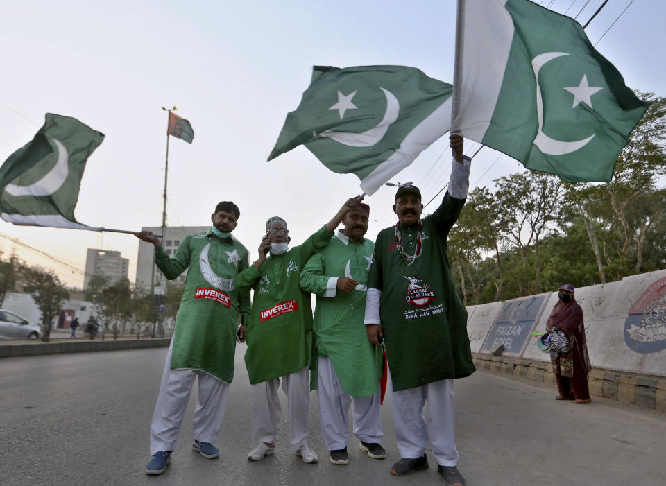 Cricket fans hold National flags while they arrive at the National Stadium to watch Pakistan Super League T20 cricket opening match between Karachi Kings and Quetta Gladiators at National Stadium, in Karachi, Pakistan, Saturday, Feb. 20 2021. Spectators returned to cricket stadiums in Pakistan for the first time since the coronavirus pandemic began when the sixth edition of the Pakistan Super League begins in the southern port city of Karachi. (AP Photo/Fareed Khan)