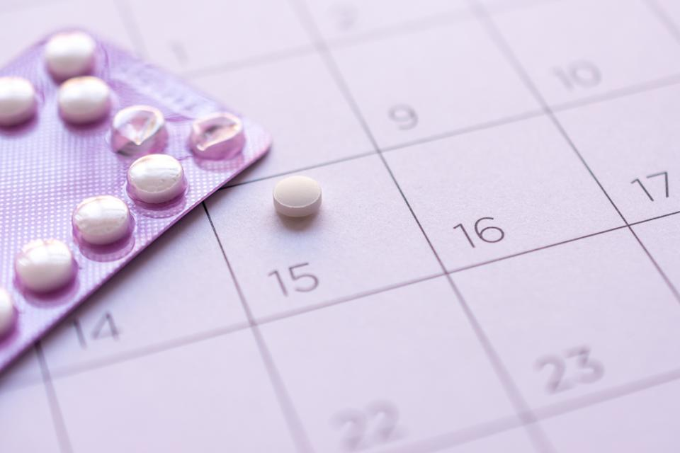 birth-control pill with date of calendar background, health care and medicine concept