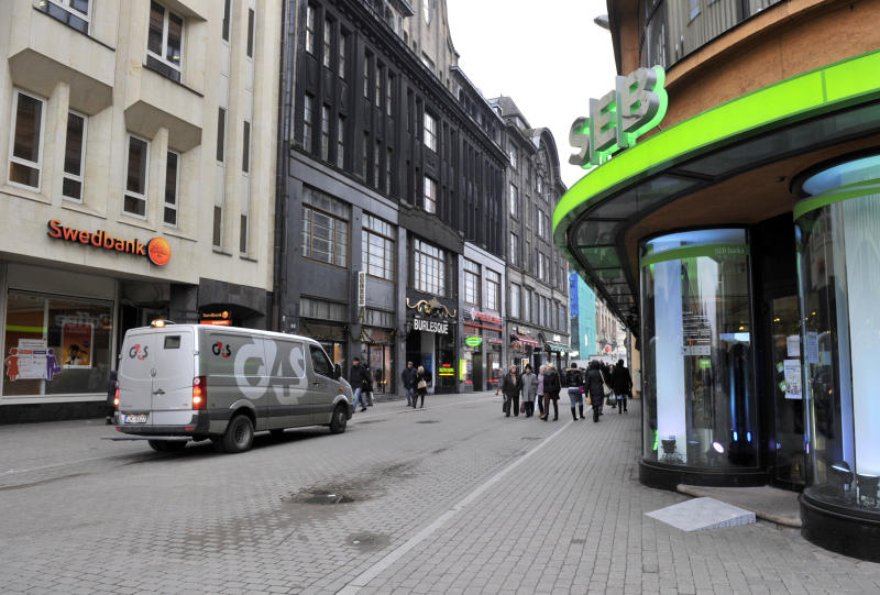 In this photo taken Friday, Dec. 27, 2013, a security van is seen outside branches of Swedbank and SEB, two of Latvia's largest banks, in downtown Riga, Latvia. When Latvia adopts the euro on Jan. 1, 2014 it will bring with it a banking sector that is swelling with suspicious money from Russia and the east - just as the currency bloc is trying to clamp down on such havens. (AP Photo/Roman Koksarov)