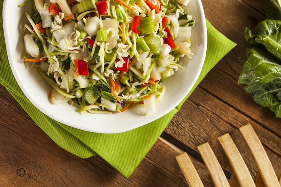 chopped salad in white bowl next to wooden fork