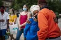 Rep. Ilhan Omar, second from right, D-Minn., greets a young voter outside the Dinkytown Target near the University of Minnesota campus in Minneapolis on Tuesday, Aug. 11, 2020. (Leila Navidi/Star Tribune via AP)