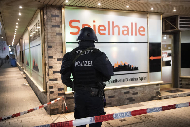 A police officer stands guard in front of a gambling hall near the scene after a shooting in central Hanau, Germany Thursday, Feb. 20, 2020. Eight people were killed in shootings in the German city of Hanau on Wednesday evening, authorities said. (Andreas Arnold/dpa via AP)