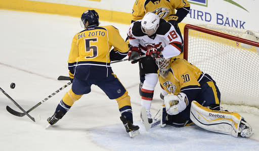 Nashville Predators defenseman Michael Del Zotto (5) and New Jersey Devils right wing Steve Bernier (18) battle for the loose puck in front of goalie Carter Hutton (30) in the second period of an NHL hockey game on Friday, Jan. 31, 2014, in Nashville, Tenn. (AP Photo/Mark Zaleski)