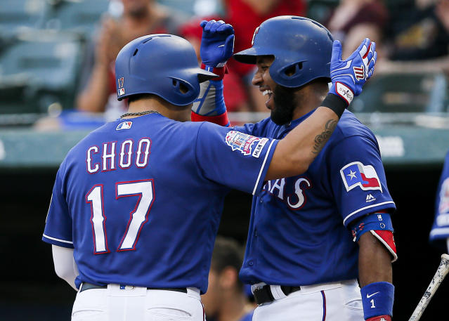 Texas Rangers' Shin-Soo Choo (17) is congratulated by Elvis Andrus after hitting a solo home run during the first inning of a baseball game against the Houston Astros, Friday, July 12, 2019, in Arlington, Texas. (AP Photo/Brandon Wade)
