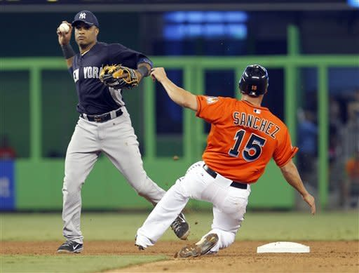 Miami Marlins' Gaby Sanchez (15) is forced out at second base by New York Yankees second baseman Robinson Cano, left, in the fourth inning of a spring training baseball game in Miami, Sunday, April 1, 2012. (AP Photo/Alan Diaz)