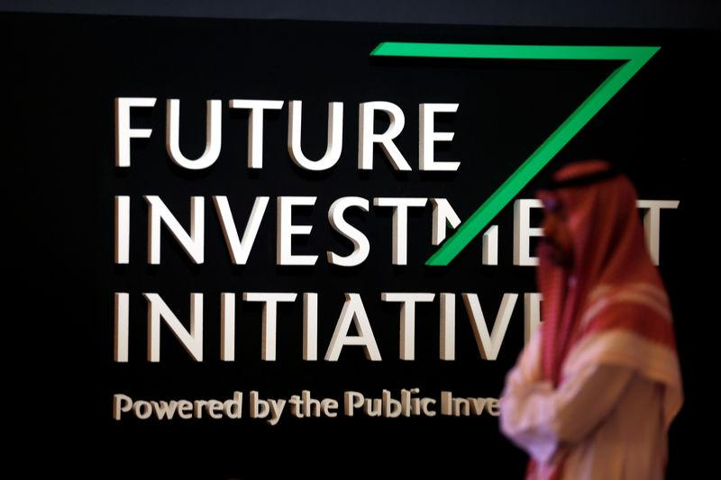A Saudi man walks past the sign of the Future Investment Initiative during the last day of the investment conference in Riyadh