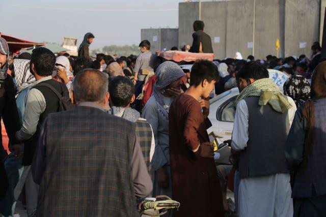 Hundreds of people gather near an evacuation control checkpoint during ongoing evacuations at Hamid Karzai International Airport