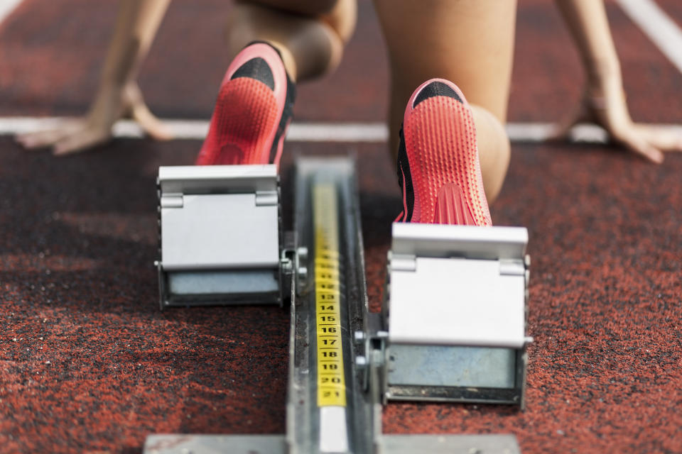 Teenage runner kneeling on starting block, close up