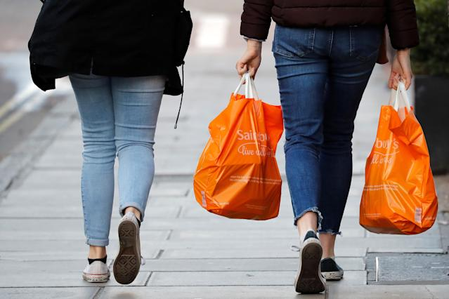 Shoppers carry their purchases in orange plastic Sainsbury's supermarket store shopping bags (Photo: Tolga AKMEN / AFP)