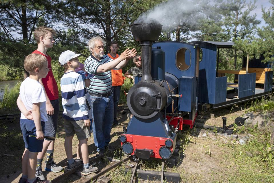 Pavel Chilin explains to children how his steam locomotive runs along his miniature personal railway in Ulyanovka village outside St. Petersburg, Russia Sunday, July 19, 2020. It took Chilin more than 10 years to build the 350-meter-long miniature personal narrow-gauge railway complete with various branches, dead ends, circuit loops, and even three bridges.(AP Photo/Dmitri Lovetsky)