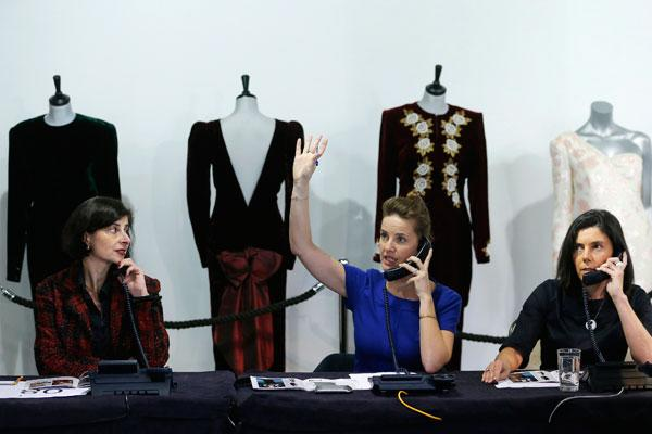 A worker takes telephone bids during the auction of ten dresses worn by Britain's Princess Diana, at Kerry Taylor Auctions in London March 19, 2013. The dresses sold for a total of 719,000 GBP (U.S.$1,085,843) on Tuesday.
