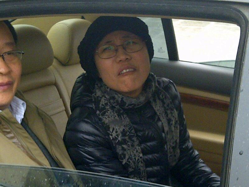 Liu Xia, wife of jailed Nobel Peace Prize winner Liu Xiabao, right, sits inside a car after attending her brother court case in Huairou's court on the outskirt of Beijing Tuesday, April 23, 2013. The brother-in-law of China's jailed Nobel Peace Prize winner Liu Xiabao has gone on trial on fraud charges that his lawyers say amount to a trumped-up case aimed at punishing the family. (AP Photo)