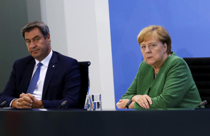 Bavarian State Prime Minister Markus Soeder and German Chancellor Angela Merkel attend a news conference following a meeting with leaders of the 16 federal states to discuss the country's response following the spread of the coronavirus, at the Chancellery in Berlin, Thursday, Aug. 27, 2020. In an effort to harmonize different coronavirus measures across the country, Germany will implement a nationwide fine for people not wearing face masks and also ban mass events until the end of the year, Chancellor Angela Merkel said Thursday. (Michele Tantussi/Pool Photo via AP)