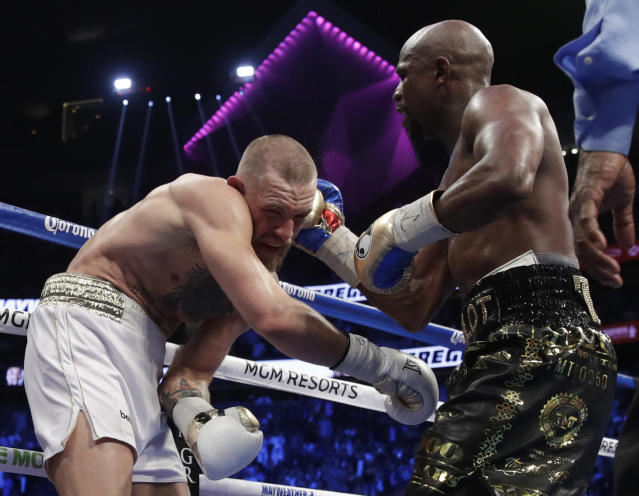 <p>Floyd Mayweather Jr. hits Conor McGregor in a super welterweight boxing match Saturday, Aug. 26, 2017, in Las Vegas. (AP Photo/Isaac Brekken) </p>