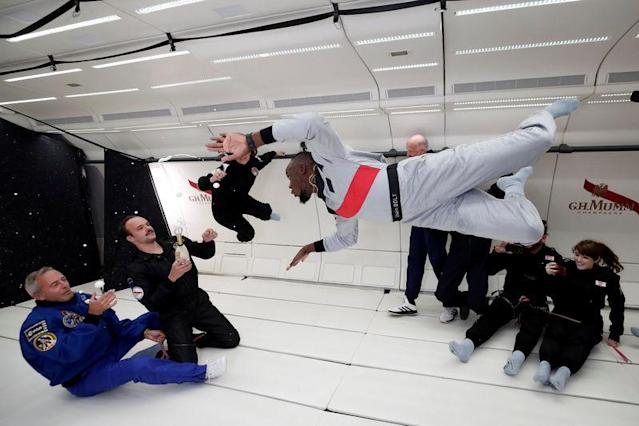 """Retired sprinter Usain Bolt, French astronaut Jean-Francois Clervoy, CEO of Novespace and French Interior designer Octave de Gaulle who designed a bottle of """"Mumm Grand Cordon Stellar"""" champagne enjoy zero gravity conditions during a flight in a specially modified Airbus Zero-G plane above Reims, France, September 12, 2018. REUTERS/Benoit Tessier"""
