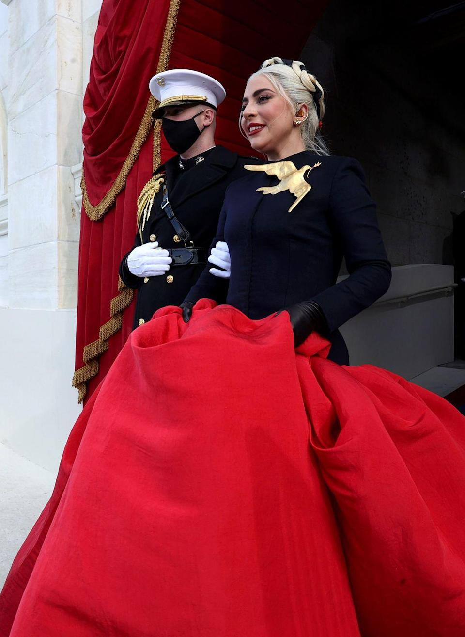 """<p>The singer, who performed the National Anthem for the ceremony, made a dramatic addition to the day's order with a custom <a href=""""https://www.schiaparelli.com/en"""" rel=""""nofollow noopener"""" target=""""_blank"""" data-ylk=""""slk:Schiaparelli"""" class=""""link rapid-noclick-resp"""">Schiaparelli</a> couture look. The navy cashmere jacket and red silk voluminous skirt left an elegant mark, but the oversized dove and olive branch brooch, more importantly, nodded to the peace, gentleness, and purity that it symbolizes across many cultures. </p>"""
