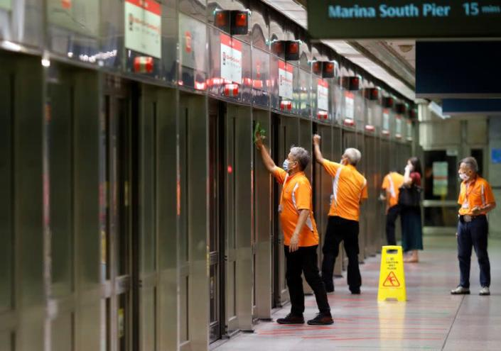 FILE PHOTO: Workers wipe down doors at a train station during the coronavirus disease (COVID-19) outbreak in Singapore