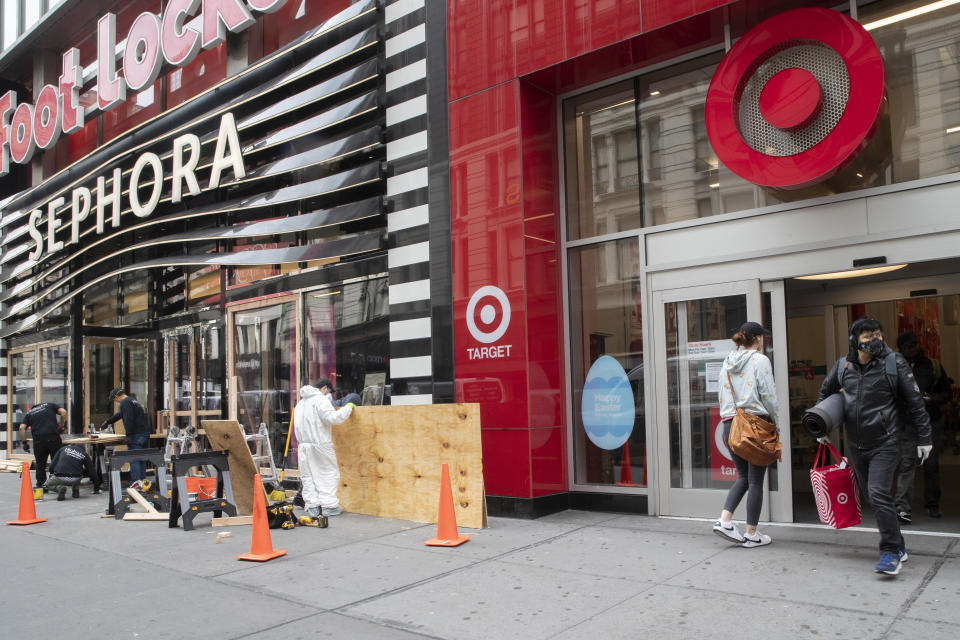 FILE - In this Friday, March 20, 2020 file photo, a shopper leaves the Target Store on 34th St. with supplies as carpenter board up the Sephora story in New York.  Target Corp. said Friday it will give a $2 an hour wage increase to its 300,000-plus workers who have been scrambling to help customers. The pay bump will be effective at least through May 2. (AP Photo/Mary Altaffer, File)