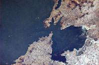 """Here is a closer view of Qingdao (Tsingtao). Much easier to see the bridge in this photo. <a href=""""https://twitter.com/Cmdr_Hadfield/status/289077421754429440/photo/1"""" rel=""""nofollow noopener"""" target=""""_blank"""" data-ylk=""""slk:(Photo by Chris Hadfield/Twitter)"""" class=""""link rapid-noclick-resp"""">(Photo by Chris Hadfield/Twitter)</a>"""