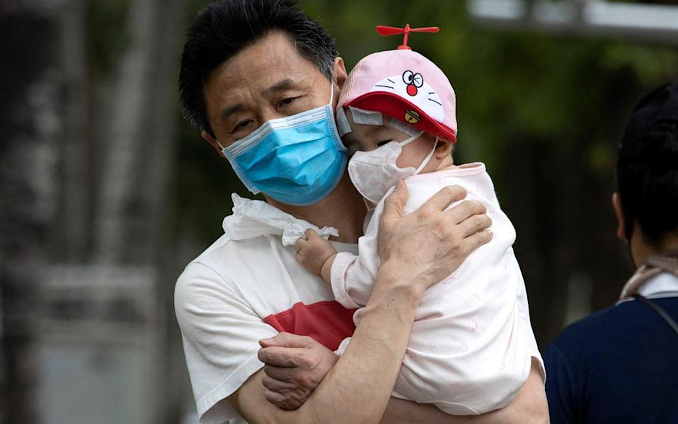 A man holds a child wearing masks to curb the spread of the coronavirus in Beijing - AP