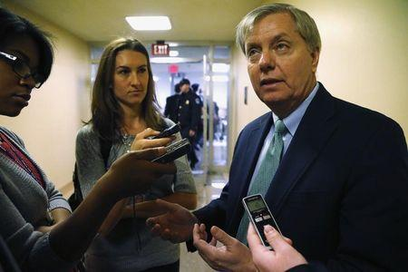 Reporters talk to U.S. Senator Graham as he arrives for weekly Republican caucus luncheon at U.S. Capitol in Washington