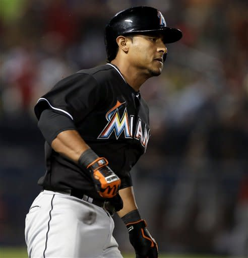 Miami Marlins' Donovan Solano hits a single to score teammate Ed Lucas in the ninth inning of a baseball game against the Atlanta Braves, Thursday, July 4, 2013, in Atlanta. (AP Photo/David Goldman)