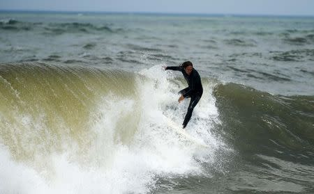 A surfer rides a wave after Hurricane Arthur in Kitty Hawk