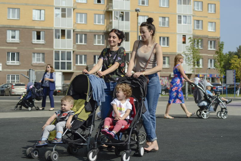 Moscow, Russia - September 1st, 2018: Unidentified women walk with their small kids at residential area in Moscow, Russia. Increase in birth rate is an important problem for Russian government.