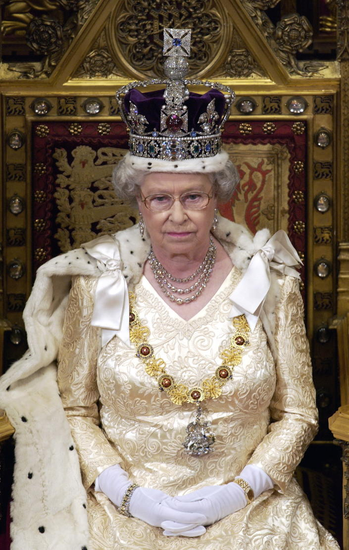 LONDON, UNITED KINGDOM - NOVEMBER 13:  Queen Elizabeth Ll Sitting On A Throne In The House Of Lords, Palace Of Westminster, Waiting To Make Her Speech During The State Opening Of Parliament.  The Queen Is Cream Satin Evening Dress Underneath Ermine-lined Robe Of State With The Imperial State Crown And The Garter Collar With A Diamond George.  (Photo by Tim Graham Photo Library via Getty Images)