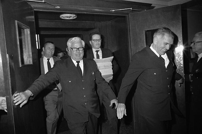 Two court officers push open doors for newsmen, who rush out of Superior Court, April 30, 1970 in Boston, with copies of the Kopechne inquest court record and Judge James A. Boyle's 12- page report. Mary Jo Kopechne died in a car accident on Chappaquiddick Island last July 18. Sen. Edward Kennedy was the driver of the car. ( \Photo: A.E. Maloof/AP)