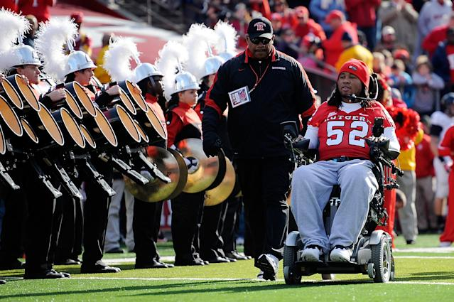 NEW BRUNSWICK, NJ - NOVEMBER 19: Eric LeGrand #52 of the Rutgers Scarlet Knights enters the stadium to be honored on Senior's Day at center field with head coach Greg Schiano of the Rutgers Scarlet Knights before a game against Cincinnati Bearcats at Rutgers Stadium on November 19, 2011 in New Brunswick, New Jersey. LeGrand was paralyzed during a kickoff return in October 2010. (Photo by Patrick McDermott/Getty Images)