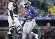 Texas Rangers' Willie Calhoun, right, scores on a single by Isiah Kiner-Falefa, next to Colorado Rockies catcher Dom Nunez during the third inning of a baseball game Wednesday, June 2, 2021, in Denver. (AP Photo/David Zalubowski)