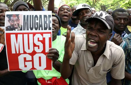 Protesters call for Zimbabwean President Robert Mugabe to resign across the road from parliament in Harare, Zimbabwe, November 21, 2017. REUTERS/Mike Hutchings