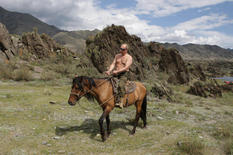 FILE - In this file pool photo taken on Monday, Aug. 3, 2009, the then Russian Prime Minister Vladimir Putin is seen riding a horse while traveling in the mountains of the Siberian Tyva region (also referred to as Tuva), Russia, during his short vacation. Putin on Wednesday, Dec. 6, 2017 declared his intention to seek re-election next March, a vote he appears certain to win. (Alexei Druzhinin, Sputnik, Kremlin Pool Photo via AP, file)