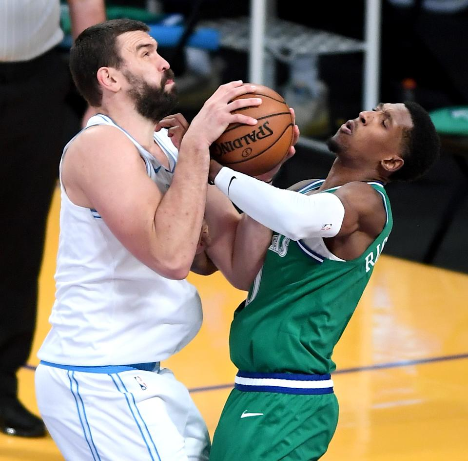 Lakers center Marc Gasol, left, is fouled by Mavericks guard Josh Richardson while attempting a shot Dec. 25, 2020.