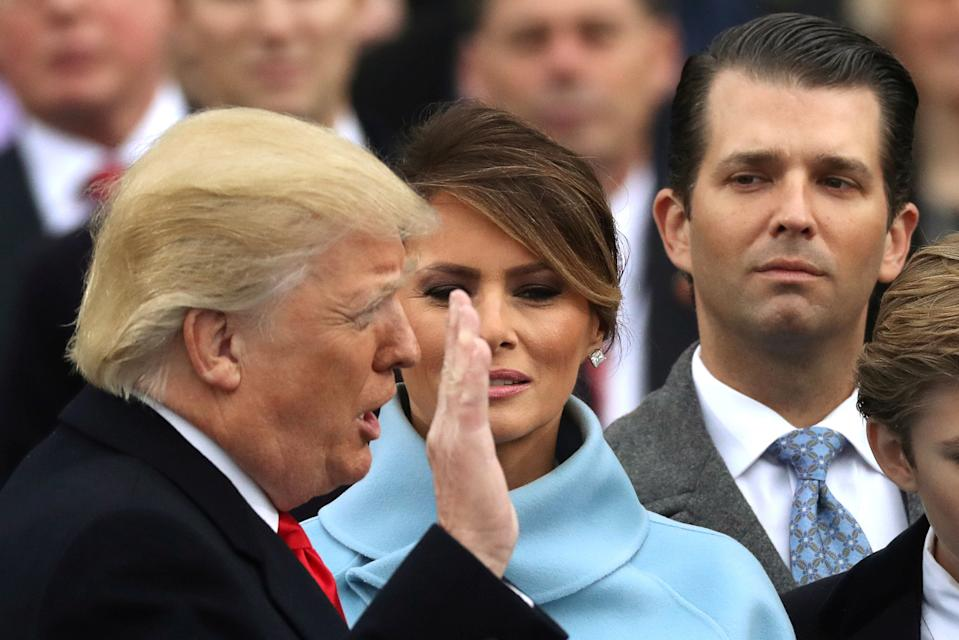 Donald Trump Jr. (R) watches as his father Donald Trump (L) is sworn in as the 45th president of the United States standing with first lady Melania Trump (C) during inauguration ceremonies at the U.S. Capitol in Washington, U.S. January 20, 2017.   REUTERS/Carlos Barria