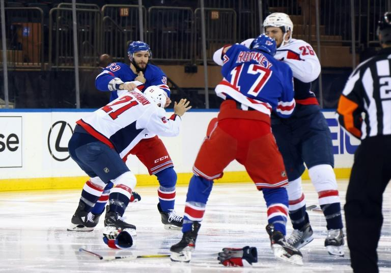 Washington Capitals' Garnet Hathaway, 21, fights New York Rangers' Phillip Di Giuseppe while Washington's Nic Dowd squares off against Rangers' Kevin Rooney, 17, in a fight-filled NHL game