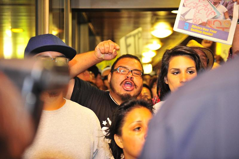 Demonstrators gathered on the steps of Anaheim City Hall Tuesday afternoon July 24, 2012 to protest the death of Manuel Diaz, 25, who died as a result of gunshot wounds sustained during a police pursuit by the Anaheim Police Department last Saturday on North Anna Drive. Riot police fired bean bag rounds and pepper balls into a crowd of protestors late Tuesday outside City Hall. (AP Photo/The Orange County Register, ) MAGS OUT; LOS ANGELES TIMES OUT