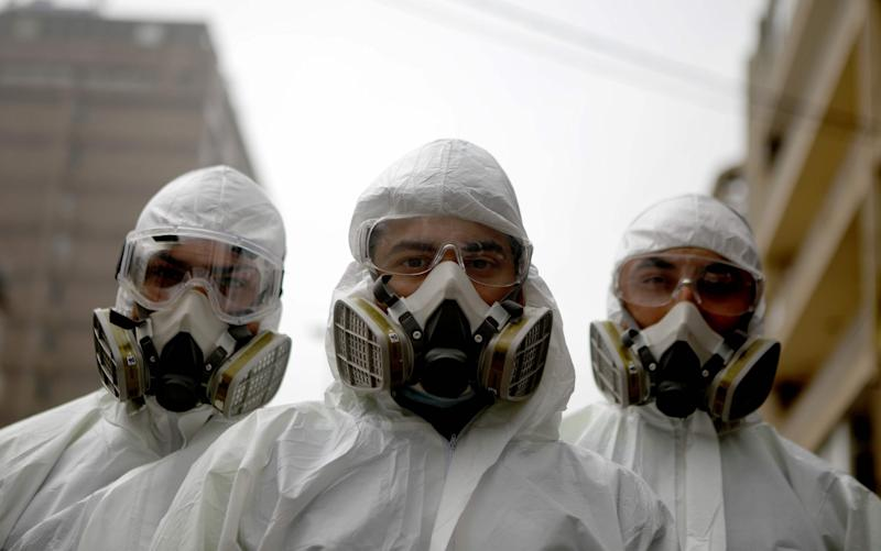 Employees of a Lebanese public health company pose with their protective gear on in Beirut  - AFP