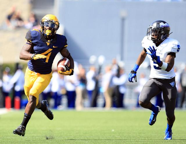 West Virginia running back Wendell Smallwood (4) carries the ball toward the end zone as Georgia State's Demarius Matthews (5) chases during the fourth quarter of an NCAA college football game in Morgantown, W.Va., on Saturday, Sept. 14, 2013. West Virginia won 41-7. (AP Photo/Christopher Jackson)