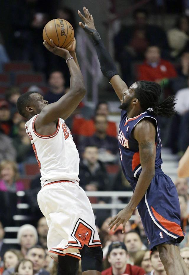 Chicago Bulls forward Luol Deng, left, shoots over Atlanta Hawks forward DeMarre Carroll during the first half of an NBA basketball game in Chicago on Saturday, Jan. 4, 2014. (AP Photo/Nam Y. Huh)